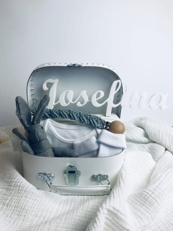 Bílý kufřík pro miminko s šedými doplňky. Neutrální barva pro obě pohlaví. Obsahuje hračku zajíce, klip na dudlík, plenku a ponožky.
