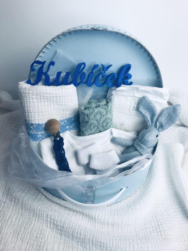 Modrý dárkový kufřík pro miminko. Obsahuje vyšívaný ručníček, mušelínovou plenku, bílé body a ponožky, zajíce a klip na dudlík