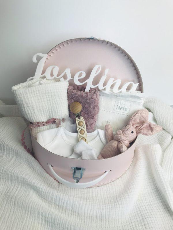Růžový dárkový kufřík pro miminko. Obsahuje vyšívaný ručníček, mušelínovou plenku, bílé body a ponožky, zajíce a klip na dudlík